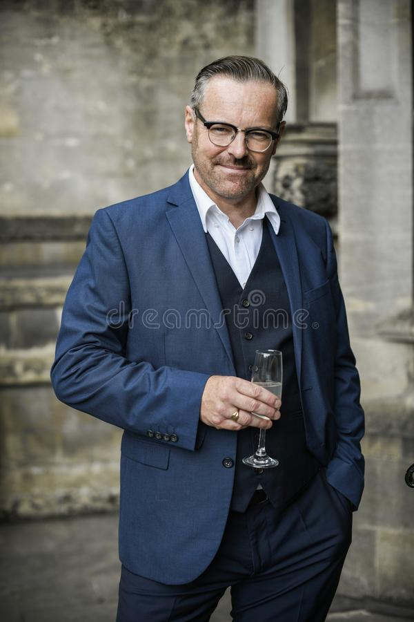 Riuscito uomo d'affari che celebra con un vetro di champagne immagini stock libere da diritti