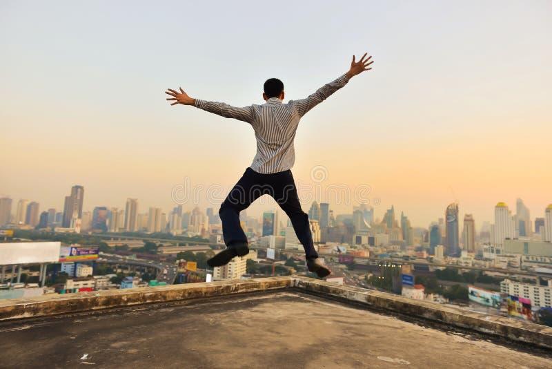 Riuscito uomo d'affari che esamina la città di Bangkok il tramonto, mani fotografia stock