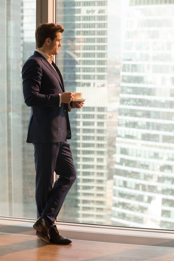 Riuscito uomo d'affari che gode del tramonto dall'ufficio fotografie stock libere da diritti