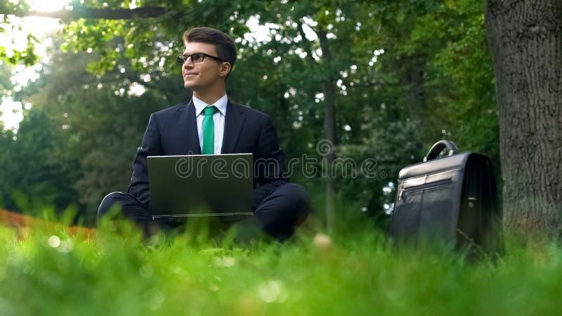 Riuscito uomo d'affari che lavora con il piacere in parco, sedentesi sull'erba, computer portatile fotografia stock
