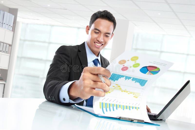 Riuscito uomo d'affari che mostra il grafico e sorridere di crescita immagini stock