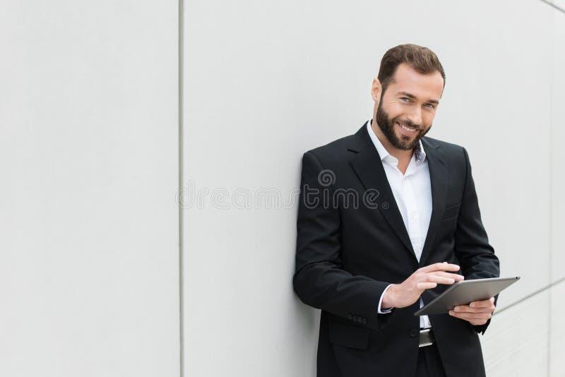 Riuscito uomo d'affari che sta facendo uso di una compressa immagine stock