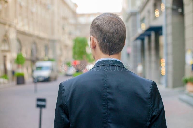 Riuscito uomo d'affari dalla parte posteriore in vestito certamente che sta nella città fotografia stock