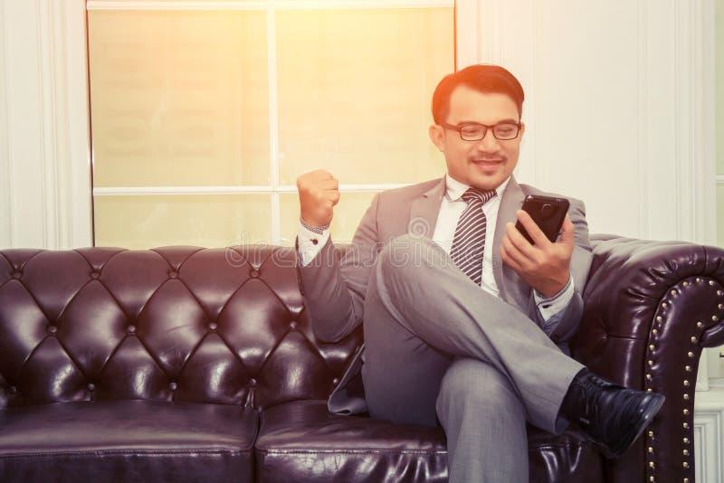 Riuscito uomo d'affari facendo uso del telefono cellulare che si siede sullo sguardo s del sofà fotografie stock