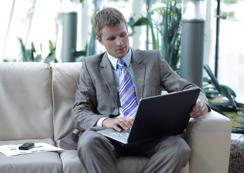 Riuscito uomo d'affari felice che si siede sullo strato all'ufficio ed al lavoro fotografie stock libere da diritti