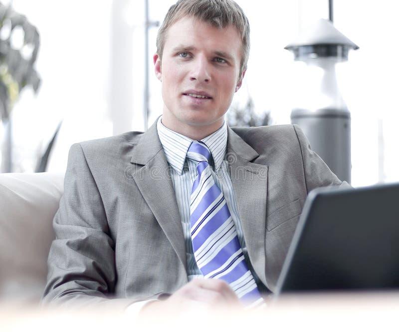 Riuscito uomo d'affari felice che si siede sullo strato all'ufficio ed al lavoro immagini stock