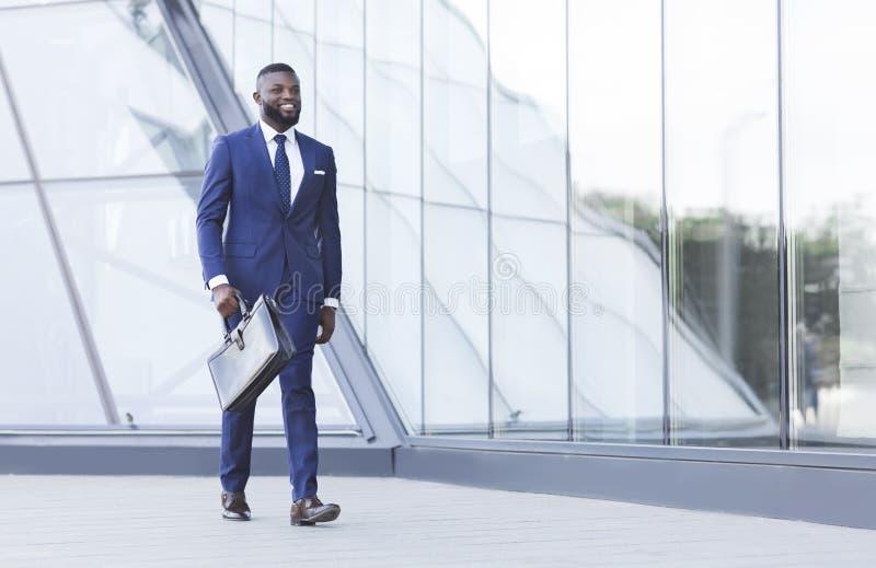 Riuscito uomo d'affari nero With Briefcase Walking nell'area urbana fotografie stock libere da diritti