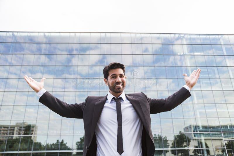 Riuscito uomo d'affari o lavoratore che sta nel vestito vicino all'edificio per uffici immagine stock