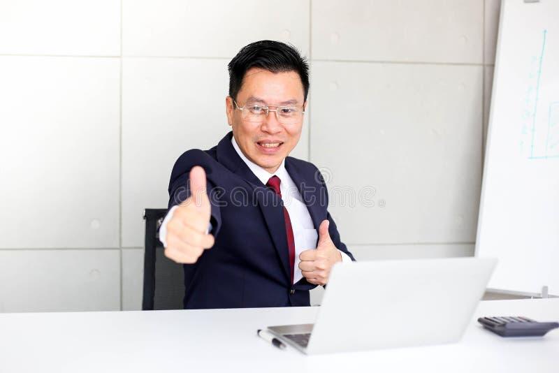 Riuscito uomo d'affari sicuro, mostrando i pollici su o come la seduta alla scrivania, successo, buona idea, grande concetto di a immagini stock libere da diritti