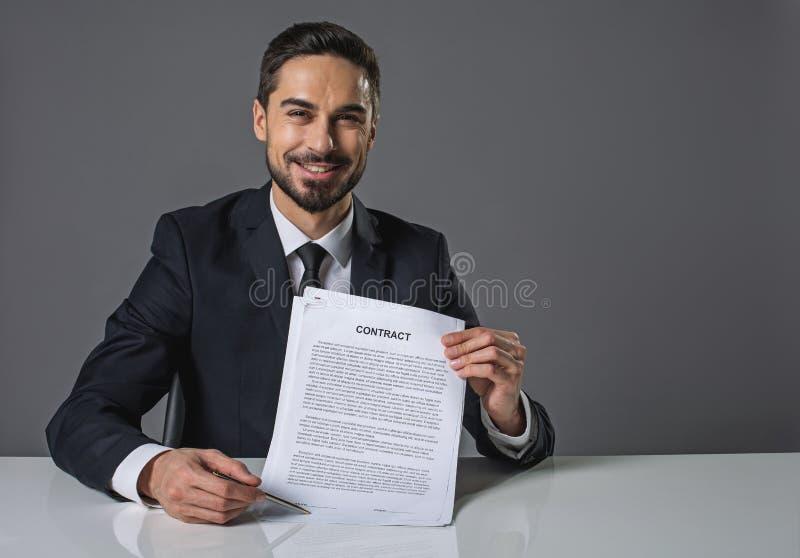 Riuscito uomo d'affari sorridente dopo la firma dell'accordo immagini stock