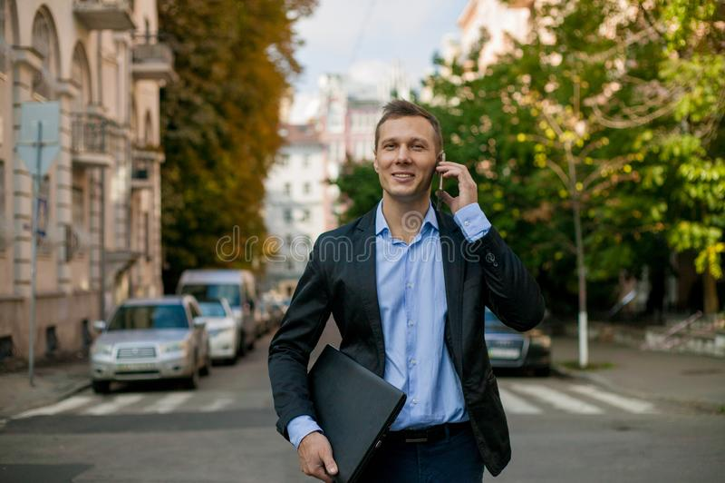 Riuscito uomo d'affari in vestito con il computer portatile nella città fotografie stock libere da diritti