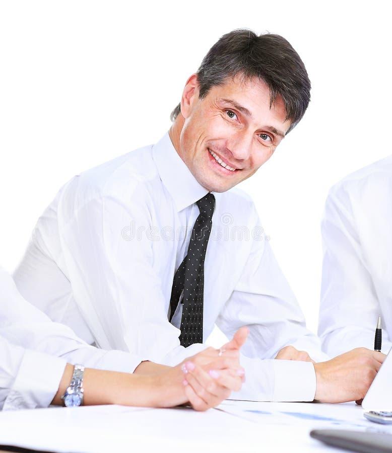 Riuscito uomo di affari su un fondo bianco, sorridente ed esaminante la macchina fotografica fotografie stock
