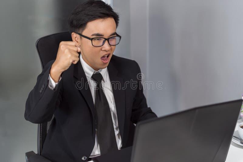 Riuscito uomo felice di affari che per mezzo del computer portatile fotografia stock