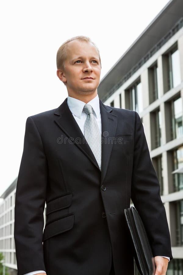 Riuscito uomo sorridente di affari in vestito nero all'aperto immagini stock