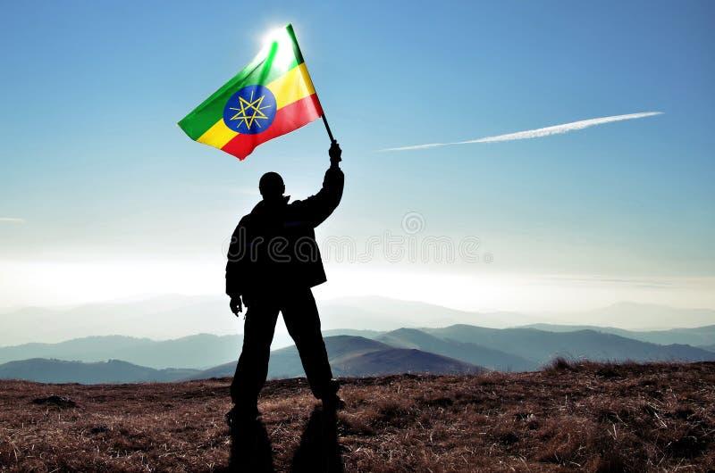 Riuscito vincitore dell'uomo della siluetta che ondeggia bandiera etiopica fotografia stock
