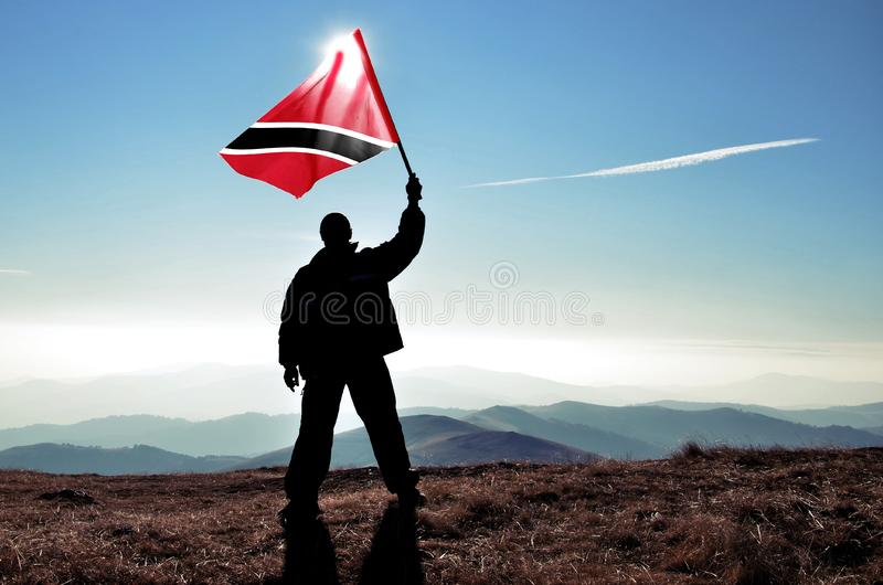 Riuscito vincitore dell'uomo della siluetta che ondeggia la bandiera di Trinidad e Tobago fotografie stock libere da diritti