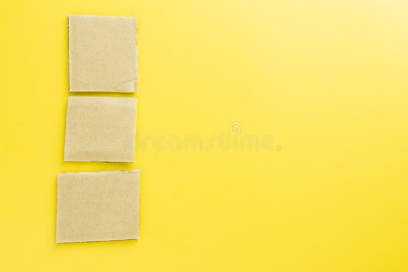 Riutilizzi la carta per appunti dalla carta della cassa su fondo giallo immagini stock libere da diritti