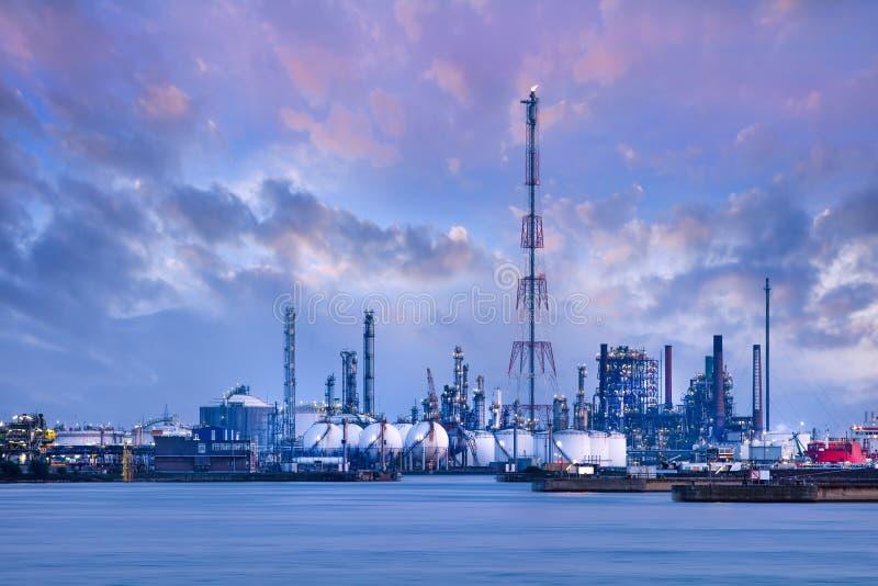Riva con l'impianto di produzione petrochimico contro un cielo blu drammatico a penombra, porto di Anversa immagini stock