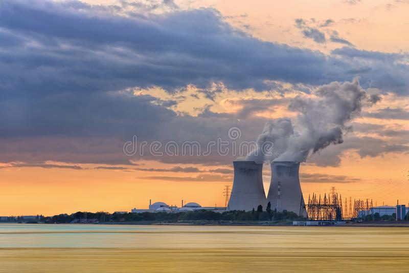 Riva con la centrale atomica Doel durante il tramonto con i cluds drammatici, porto di Anversa fotografia stock