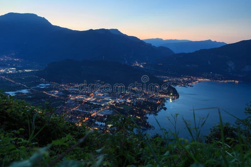 Riva del Garda πόλης πανόραμα στη λίμνη Garda και τα βουνά τη νύχτα πριν από την ανατολή στοκ εικόνες