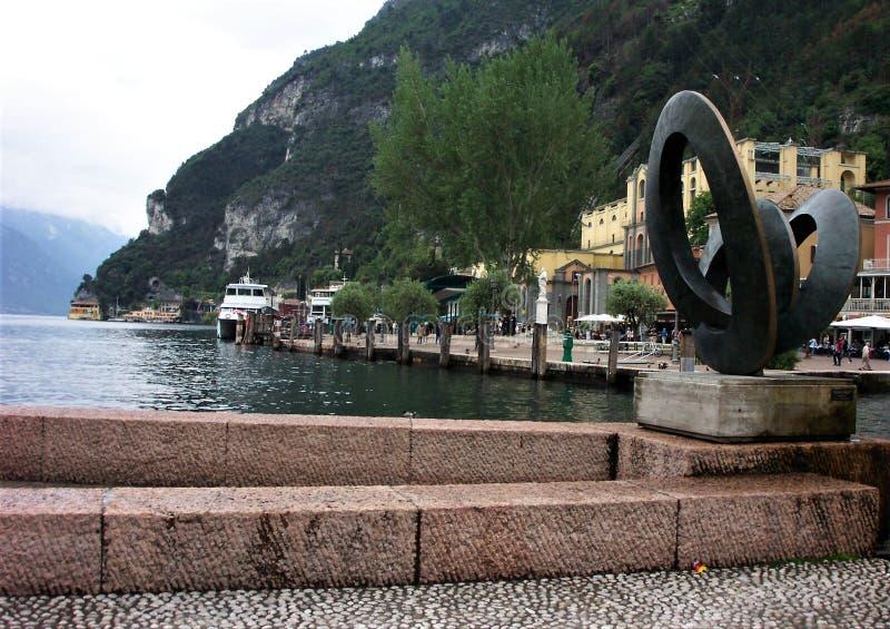 Riva del Garda, Italy. Art sculpture, buildings and view of Lake Garda at Riva del Garda town square, Veneto, Italy stock photography