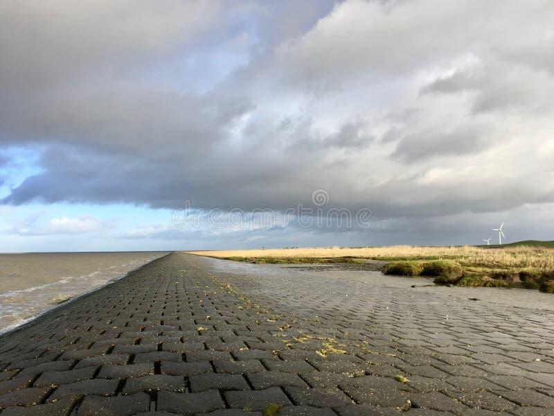Riva del Mare del Nord in Frisia orientale Ostfriesland con le nuvole e la luce drammatiche immagini stock