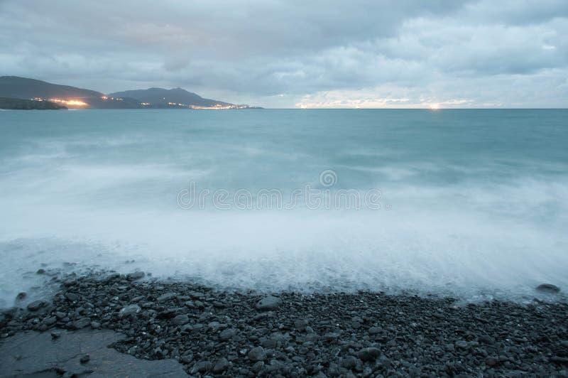 Riva della spiaggia rocciosa in un tramonto tempestoso immagine stock libera da diritti