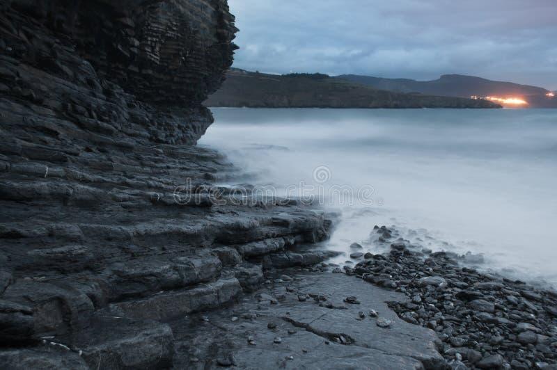 Riva della spiaggia rocciosa in un tramonto tempestoso immagine stock