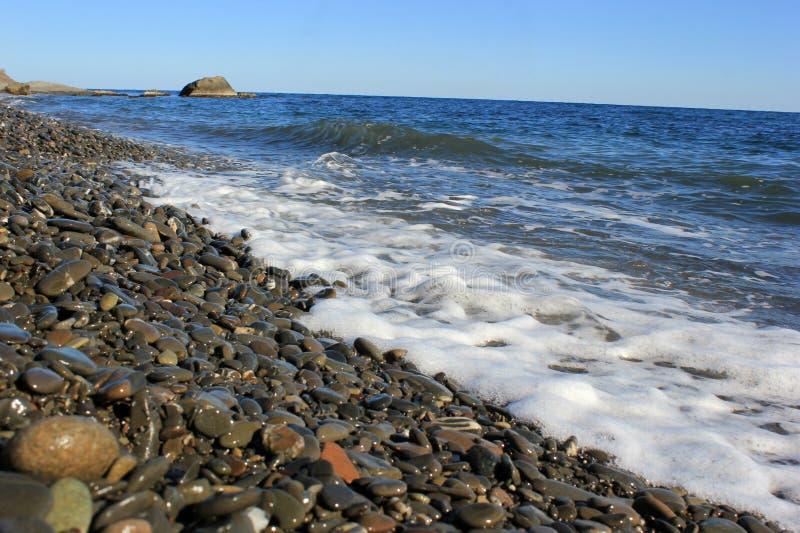 Rivage de la mer bleue, pierres grises lisses sur le rivage photographie stock libre de droits