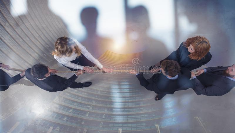 Rival business man and woman compete for the command by pulling the rope. double exposure royalty free stock photos