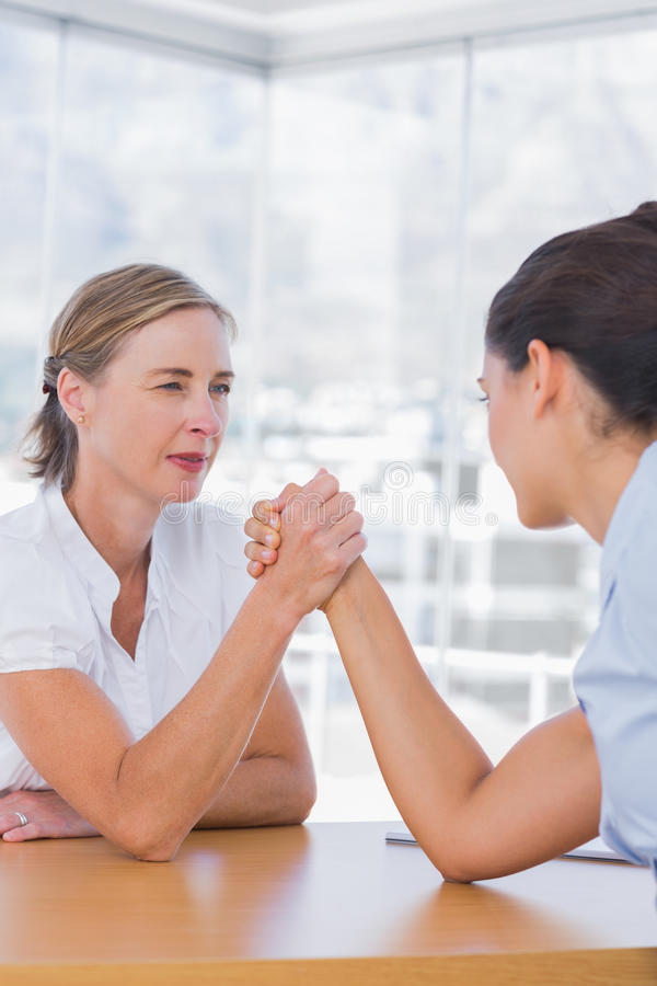 Rival businesswomen having an arm wrestle. In their office stock photos