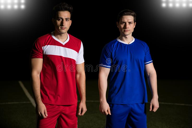 Rival soccer players on field. Two rival football team players standing together on field royalty free stock photography
