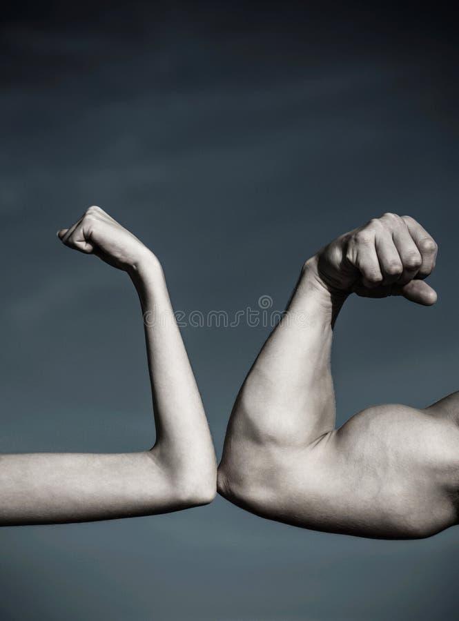 Rivalidad, contra, desafío, comparación de la fuerza Brazo muscular contra la mano débil Contra, lucha difícilmente Competencia,  imágenes de archivo libres de regalías