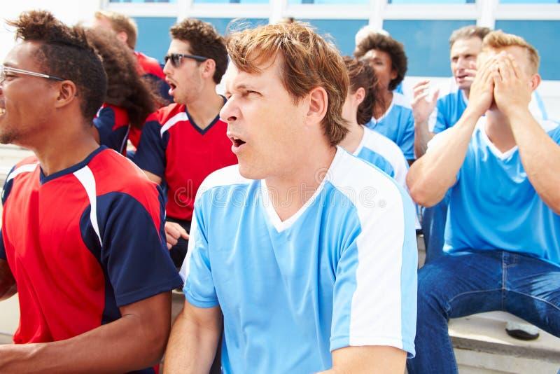 Rivaliserande åskådare som håller ögonen på sporthändelse royaltyfri bild