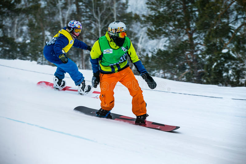 Rivalry between two young men snowboarders downhill stock images