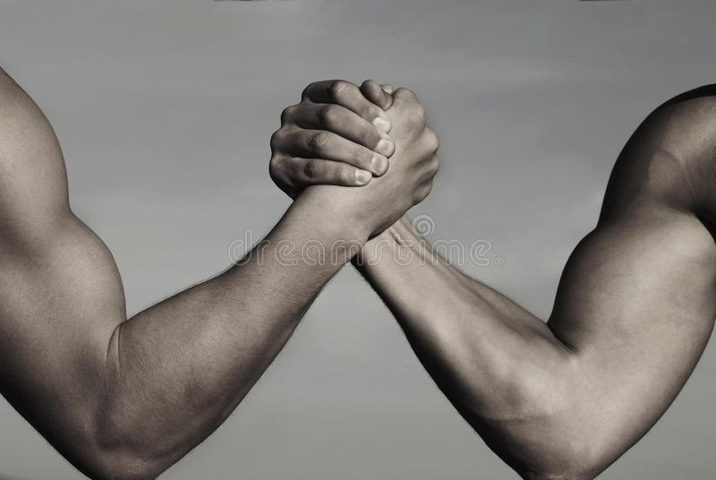 Rivalry, vs, challenge, strength comparison. Two men arm wrestling. Arms wrestling, competition. Rivalry concept - close royalty free stock image