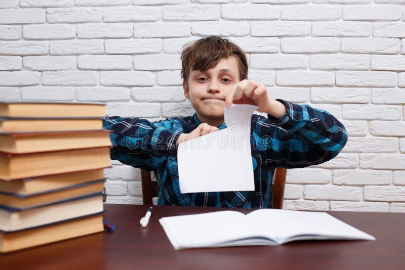 Rivande legitimationshandlingar för stressad och utmattad skolpojke som sitter på Det royaltyfria bilder