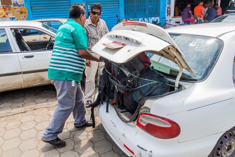 RIVAS, NICARÁGUA - 1º DE MAIO DE 2016: O taxista está fixando a bagagem de tamanho grande na vila de Rivas, Nicarag imagem de stock