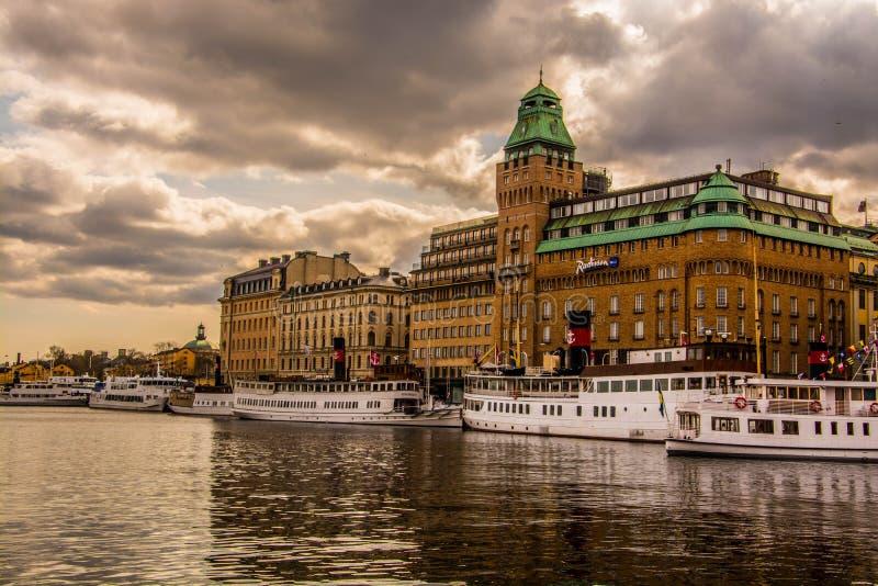 Rive à Stockholm avec les nuages et l'hôtel dramatiques photographie stock libre de droits