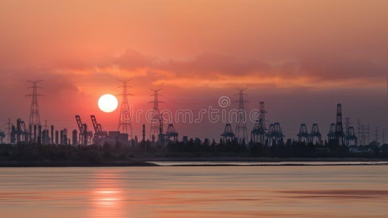 Rive avec des silhouettes des grues de terminal de conteneur pendant un coucher du soleil, port d'Anvers, Belgique image stock