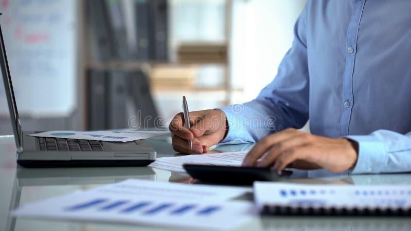 Rivenditore della società che conta calcolatore e che riempie rapporto, sedentesi alla tavola dell'ufficio immagine stock libera da diritti