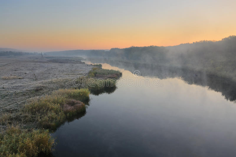 River of autumn. Cold morning landscape with a river. Grass covered by hoarfrost stock photos
