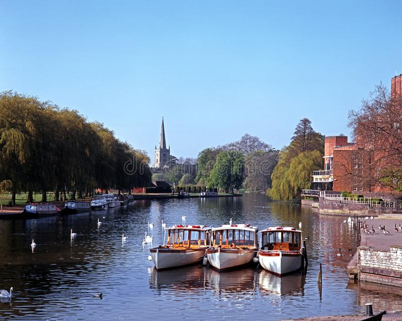 River Avon, Stratford-upon-Avon, UK. River Avon with pleasure boats moored and Church to rear, Stratford-upon-Avon, Warwickshire, England, UK, Western Europe stock image