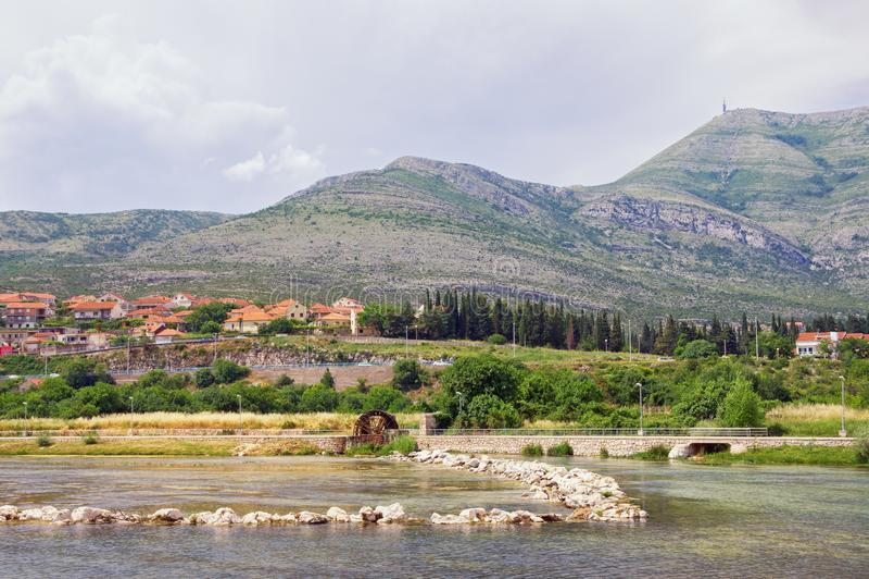 River bank with small dam and water wheel. Bosnia and Herzegovina, view of Trebisnjica river. River bank with small dam and water wheel. Bosnia and Herzegovina stock photos