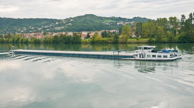 River barge cursing on the Rhone river on a cloudy day. River barge cursing on a calm Rhone river on a cloudy, cold, rainy, overcast, late afternoon, autumn day royalty free stock photo