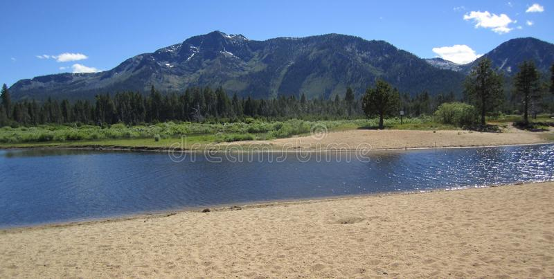 River beach in South Lake Tahoe with mountains in the background. Scenic view of a sand and gravel beach along a river in South Lake Tahoe California. Blue sky stock photography
