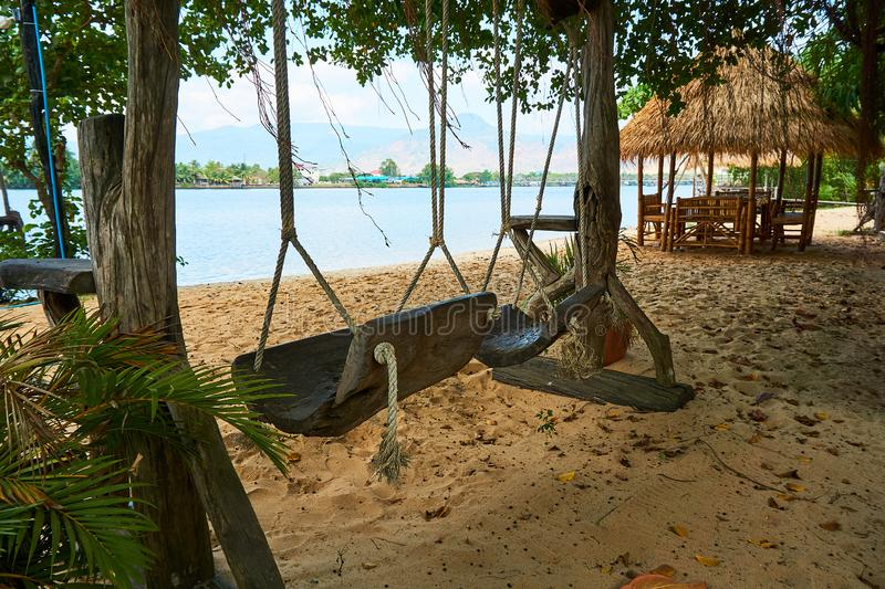River beach with straw hut and swing in Kampot Cambodia. River beach with straw hut in Kampot Cambodia sunny day travel stock images