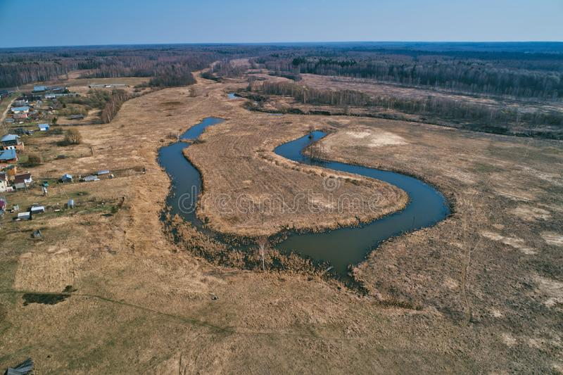 River bend in the shape of a horseshoe. Aerial view. Early spring, landscape with dead grass royalty free stock photo