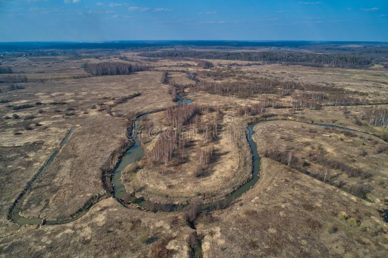 River bend in the shape of a horseshoe. Aerial view. Early spring, landscape with dead grass stock photography