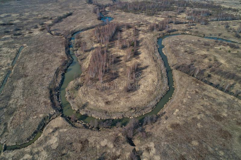 River bend in the shape of a horseshoe. The view from a great height. Early spring, landscape with dead grass stock images